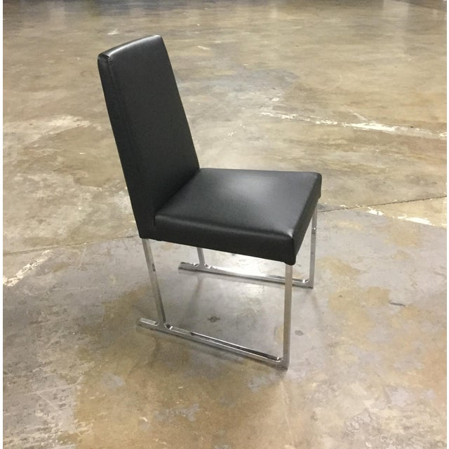 Camerich contemporary dining chair featuring tapered rear chrome legs supporting a high-resilient foam seat cushion and...
