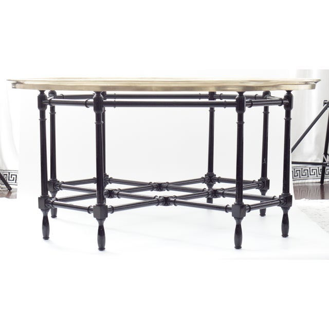 Large midcentury coffee table with brass-rimmed glass top and wooden bamboo-style stand. Faux Bamboo motif base is in a...