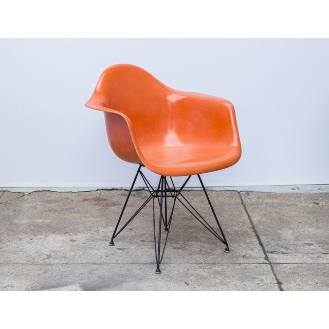 Classic Charles and Ray Eames 1960s molded fiberglass armchair in orange on a reissued black Eiffel base for Herman...