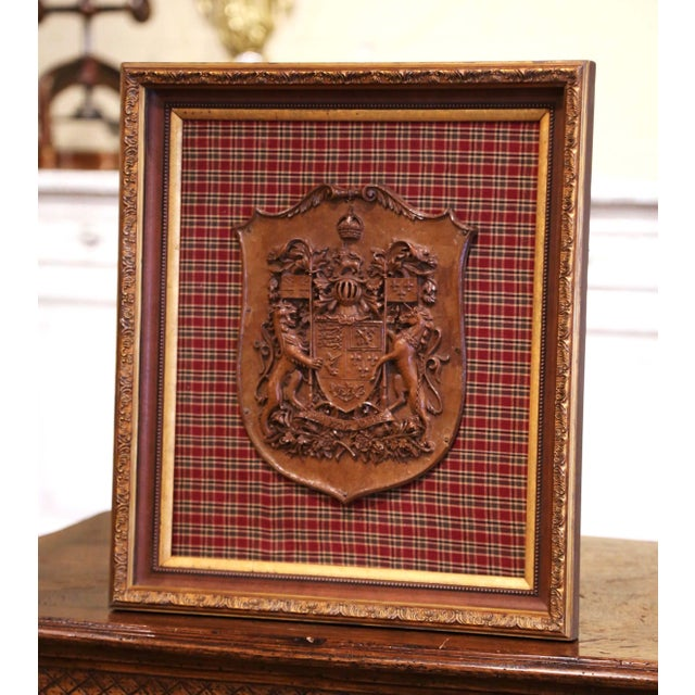 Crafted in France circa 1880 and set on a colorful plaid background fabric, the elegant framed shield features the coat of...