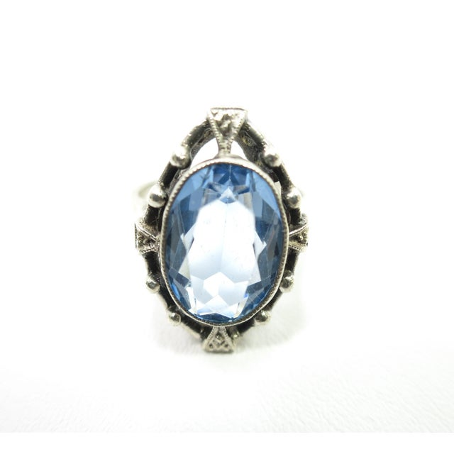 Offered here is an Edwardian 835 silver and blue topaz ring from about 1910. The oval faceted pale blue topaz stone is...