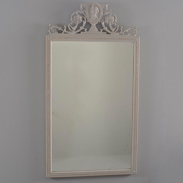 Circa 1890 pair of directoire style wood framed mirrors with antique white painted finish feature beveled edges and...