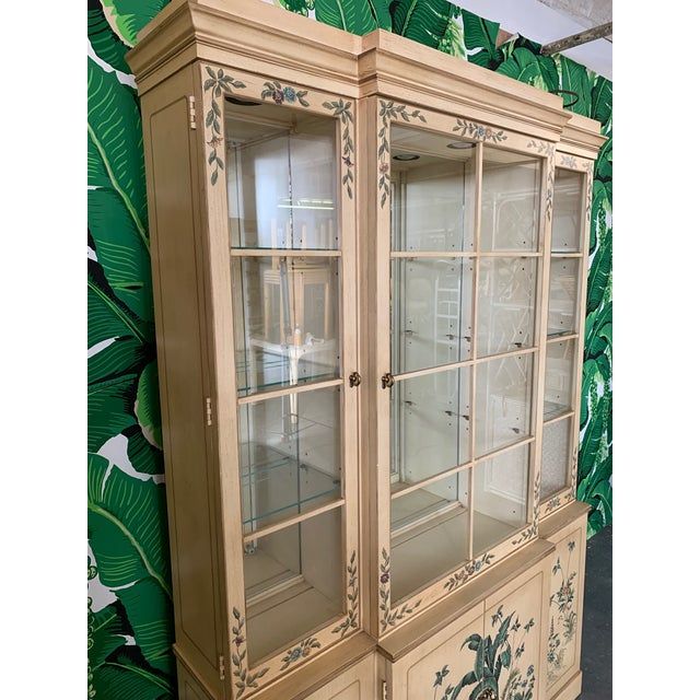 Vintage Drexel china cabinet features hand painted banana leaf detailing and mirrored back. Glass shelving and ample...