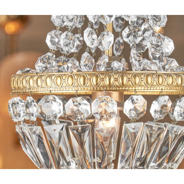 Empire style crystal chandelier with a gilt brass, embossed structure and details from France. This piece features a...