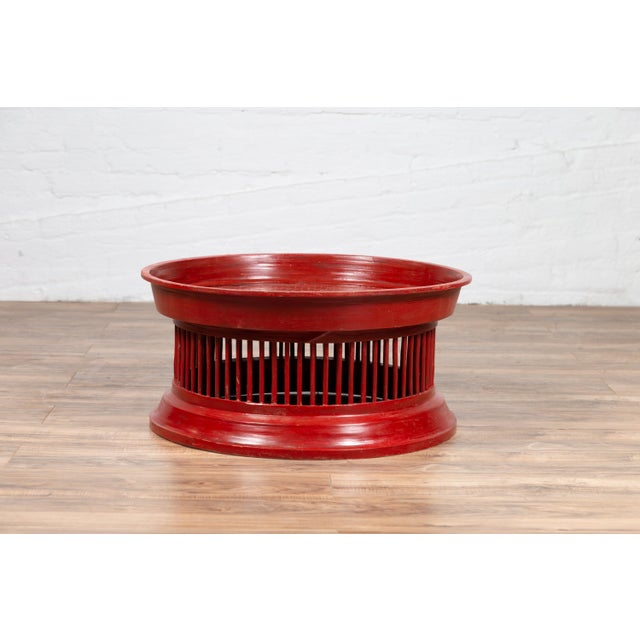 A Thai contemporary rattan drum coffee table with red lacquer, inspired by an antique tribal tray. This Thai coffee table...
