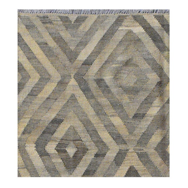 This beautiful Kilim is hand made, made in Afghanistan. It features a geometric pattern in a vibrant combination of ivory...