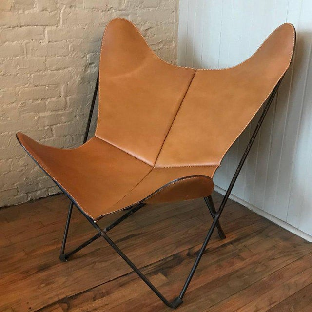 Vintage, mid century modern, butterfly chair by Jorge Ferrari-Hardoy for Knoll International features a tan luggage...