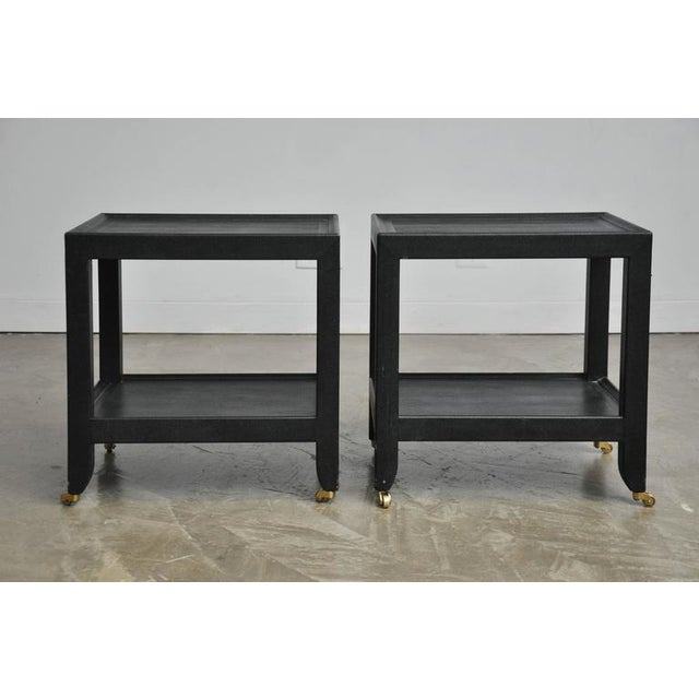 Pair of large-scale telephone side tables by Karl Springer. Black lizard skin with brass wheels. Will be accompanied with...