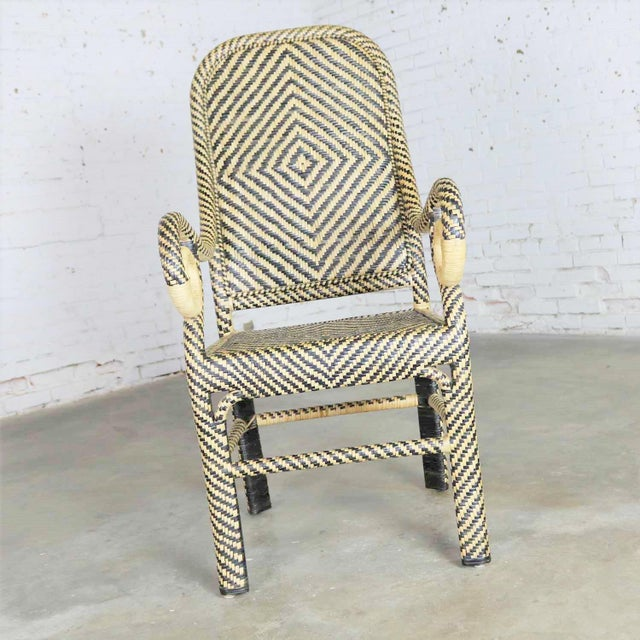 Handsome vintage two-tone rattan wicker chair with a chevron pattern, spiral arms and a tall rounded back. It is in...
