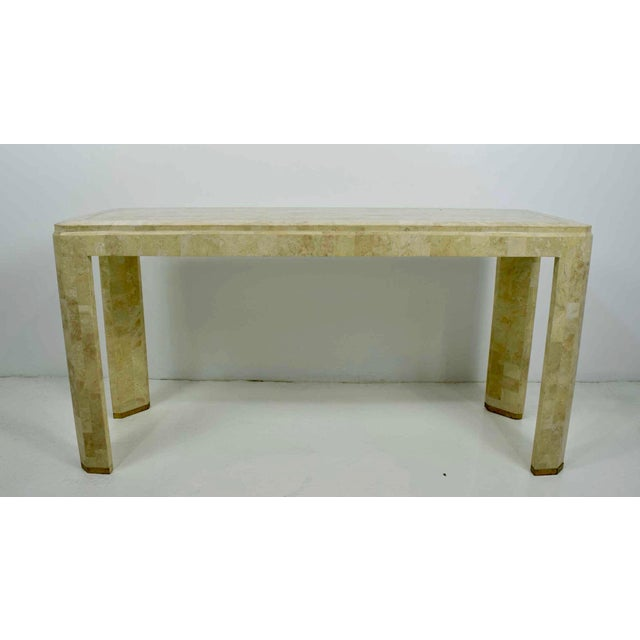 Maitland-Smith console. Tessellated marble in a mosaic pattern, brass inlay on top and brass caps on legs. We have a...