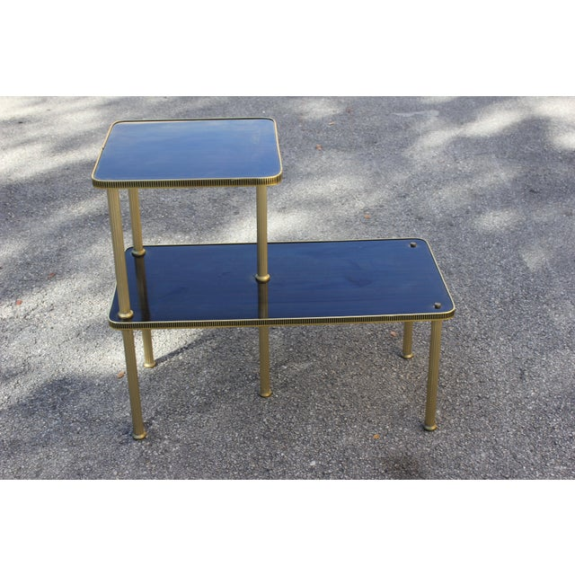 French art deco period accent, gueridon or side table, circa 1940. Mahogany and brass, two-tier supported by five brass...