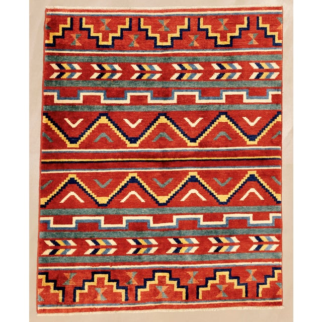 A hand knotted wool rug of Southwest Pueblo design. A new, unused rug, vividly colored with tiered rows of geometric...