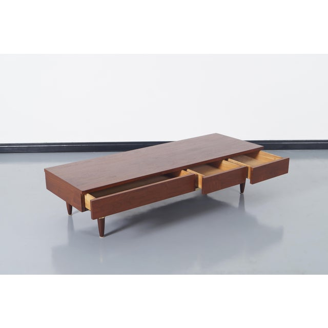 Vintage walnut & brass bench / coffee table designed by Merton Gershun for American of Martinsville. Features three...