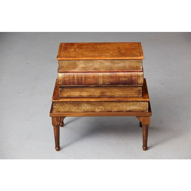 Four graduate oversize faux leather volumes with gilt tooling raised on a wood table base. Hinged top revealing a deep...