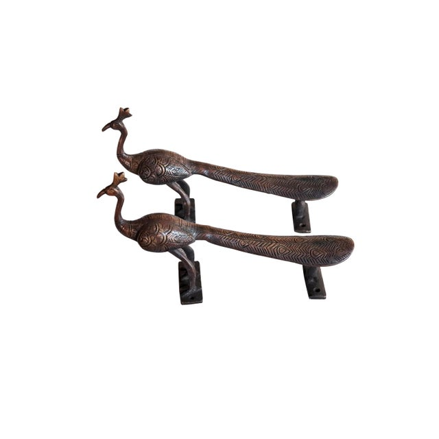 A pair of large dark brass peacock door handles or cabinet pulls. Hollywood Regency in style, with intricate carving...
