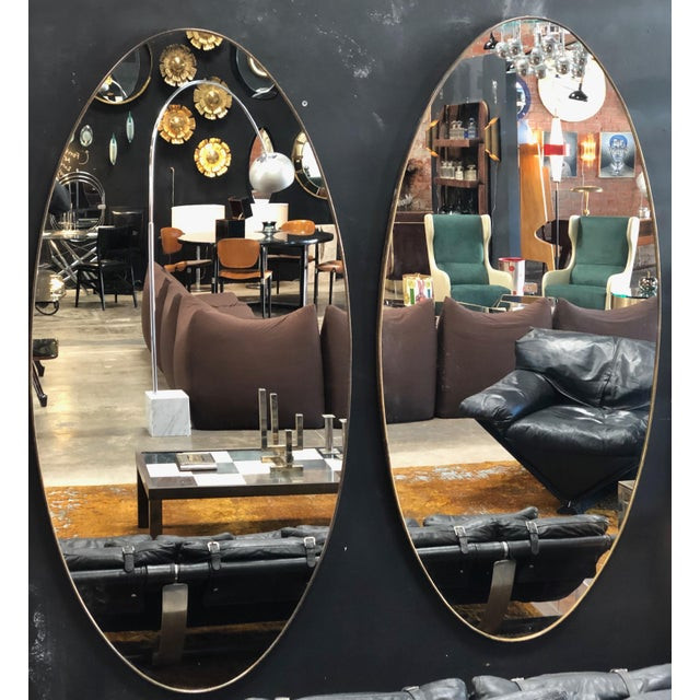 A pair of glamorous oval shaped mirrors with a metallic finish, Italy, late 1960s.