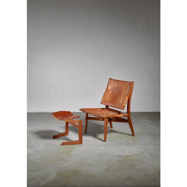 A wooden lounge chair with a brown saddle leather sling seating with a matching ottoman, made by an American craftsman....