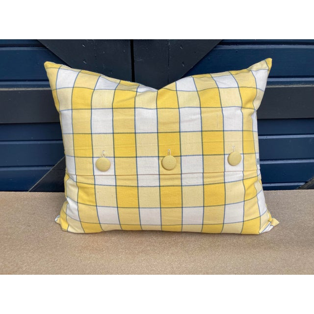 A pillow made from a mid century block printed linen, backed with a complementary yellow and white check cotton. A down...