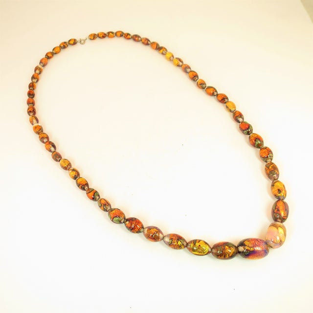 Offered here is a 1950s beaded necklace of graduated hand-blown Venetian fire opal foiled glass beads in a variety of...