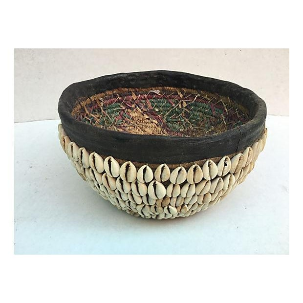 Handwoven basket decorated with shells attached to raffia with leather trim from the Nigerian Hausa tribe. Some wear.