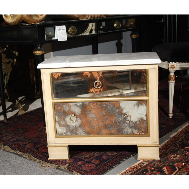 Pair of cream painted and smoke glass front marble top nightstands with two drawers. Standing on block feet.