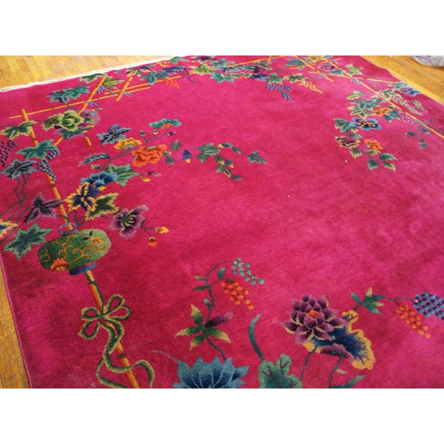 "This is a Chinese art wool rug from China 1920. The size is 8'8""x11'. The color is pink with patterns in green, blue,..."