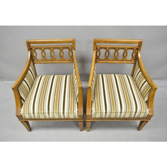 Pair of Hollywood Regency French Style Carved Spiral Back Arm Chairs. Item features striped upholstered seats, carved...
