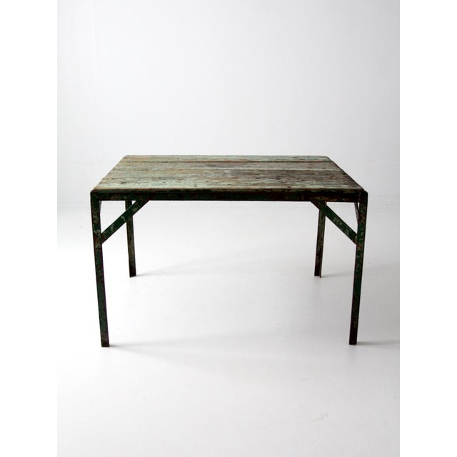 This is a vintage industrial wood top table. It features a green metal frame with a painted wood slat top. Stunning...