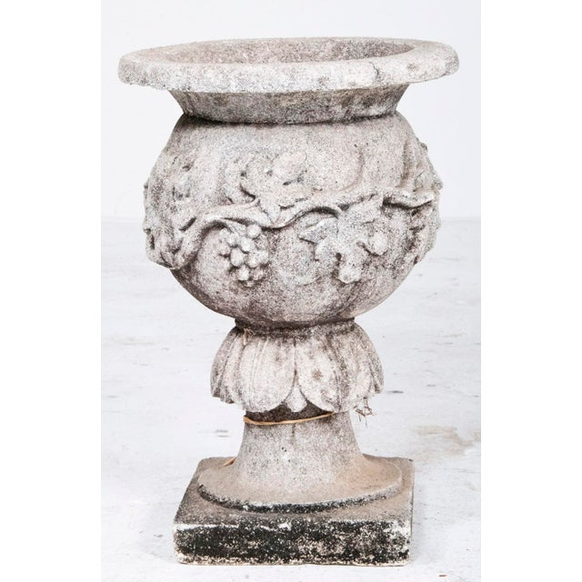 Vintage cast stone garden urn on stand. The urn is carved with a grape vine, leaves and grapes.