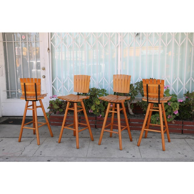Vintage set of 4 Arthur Umanoff Style Slat Bar Stools in excellent condition. No damages on the wood. They swivel well and...