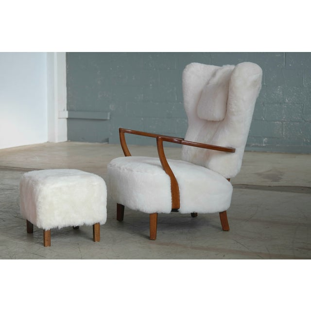 Beautiful Danish mid-century highback lounge chair with ottoman with Fritz Hansen style open armrests in carved beech wood...
