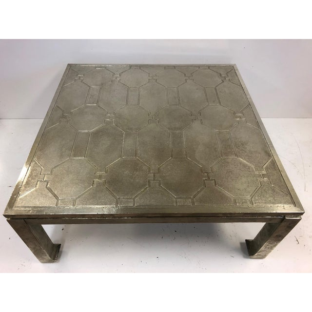 Modern, silver clad coffee table. The table has a wooden base with a clad silver, sheet metal etched decorative pattern.