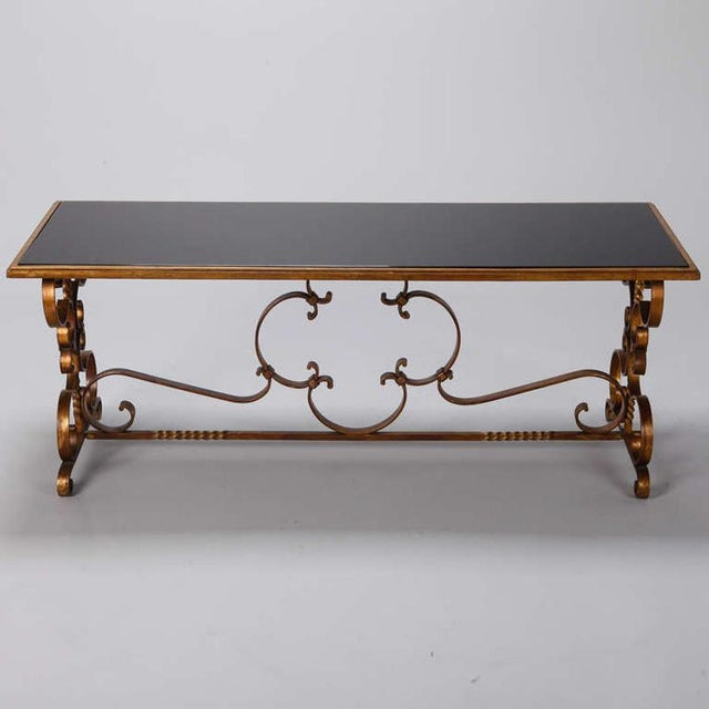 Circa 1930s Italian low cocktail / coffee table with gilded iron base, scrolled feet and black glass table top.