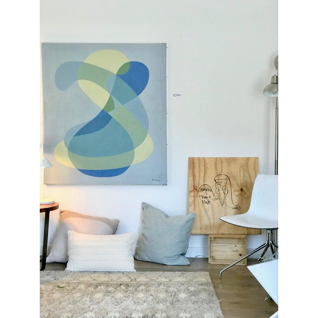 . The amorphous intertwining and overlapping shapes and the bright sky blue background is a hallmark of the emerging...