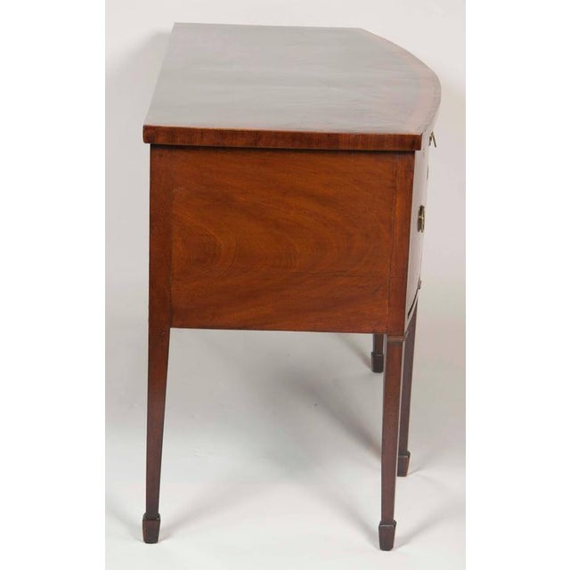 Bowed top with crossbanded edge over a long cutlery drawer flanked by a bottle drawer and a deep drawer, with fan inlaid...