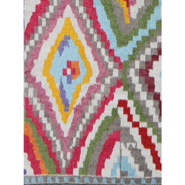 This hand-knotted Turkish Tulu rug features a modern design in a variety of vibrant colors, including yellow, blue, red,...