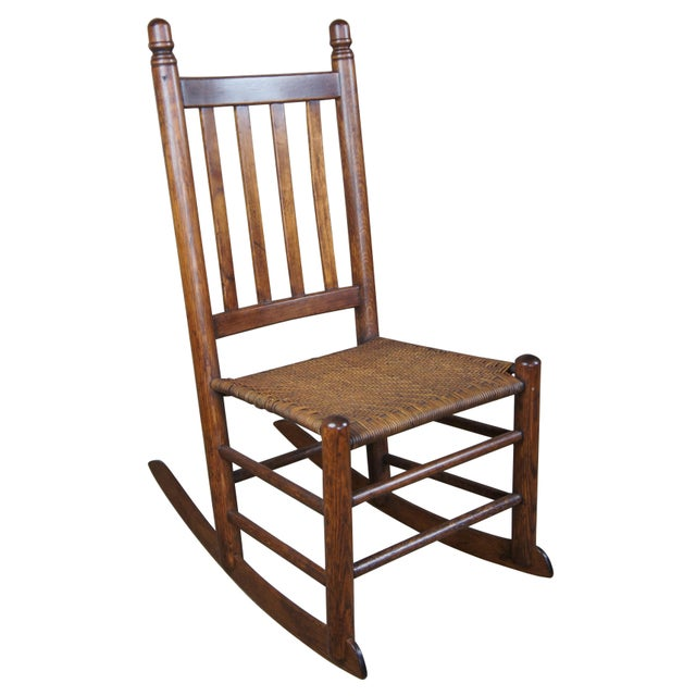 Early 20th century oak rocking chair, features acorn finials, a slat back and rattan / wicker seat.