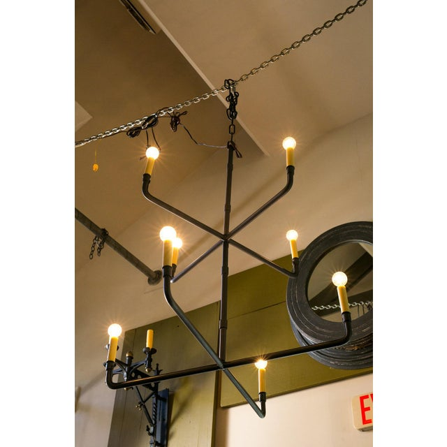 Two-tier hand-made iron chandelier of simple design. Eight alternating arms with candelabra-size sockets (each...