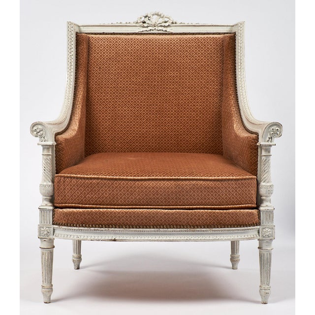 Beautiful hand carved and painted French antique bergere with crisp neoclassical details of florals and bows. The fluted...