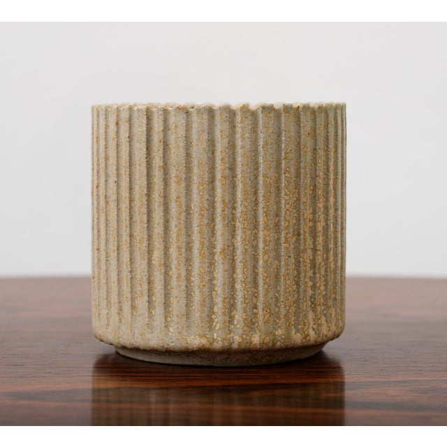 A small circular stoneware vase by Arne Bang with fluted exterior in a bisque glaze, Denmark, 1950's.