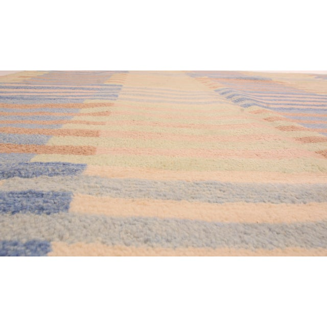 Originating from India, this geometric hand-knotted wool rug employs a borderless, contemporary all over field design...