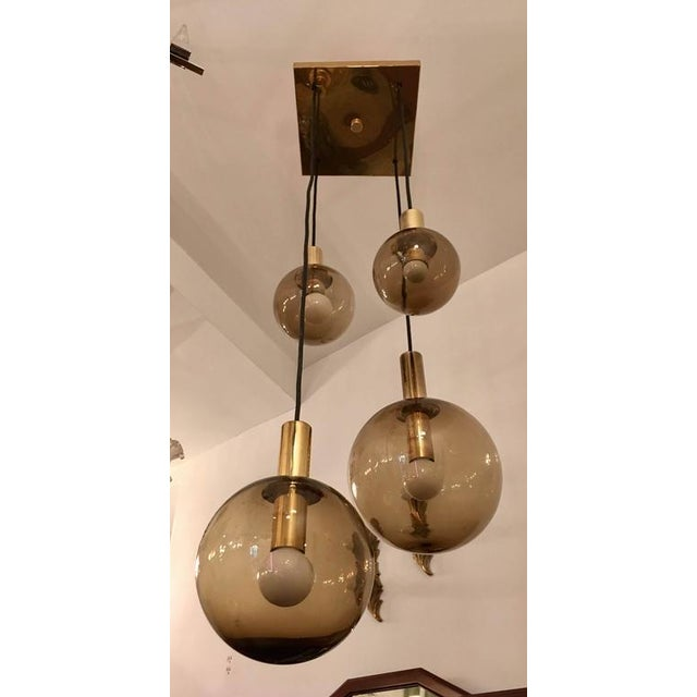 A great original 1970 high style chandelier composed of a square polished brass fixture and four smoked glass globe...