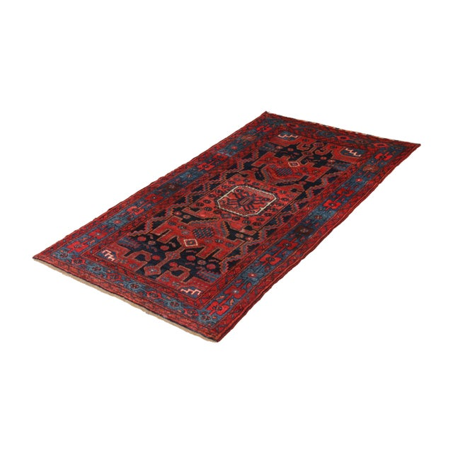 Hand-knotted in wool originating circa 1890-1900, this antique Persian rug connotes a traditional Mosul rug design (Musel...