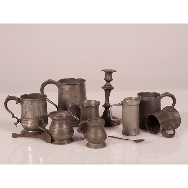 A set of eleven English pewter culinary pieces including two spoons and a candlestick circa with various measure marks and...