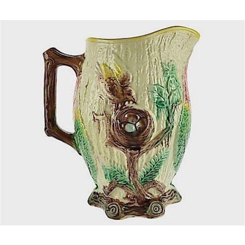 Large antique majolica pitcher decorated with a bird at a nest filled with eggs. Beautiful leaf decoration at handle. 19th...