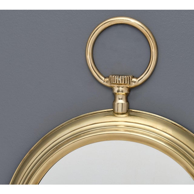 A French brass vintage pocket watch mirror from the Art Deco period with a circular central mirror.