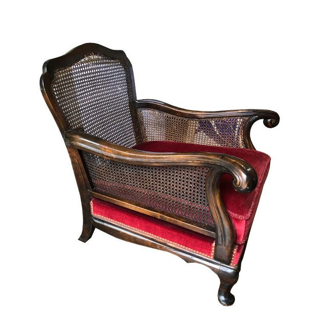 Red velvet carved wood Bergere or Charles of London Chair. In the style of Louis XVI. Chair features a cane back and...