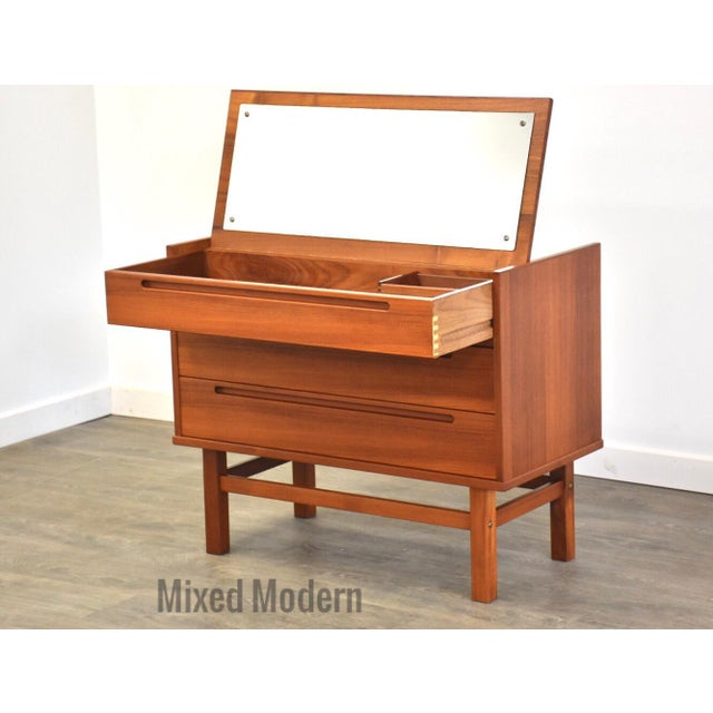 A mid century modern teak two drawer dresser chest with a flip top vanity designed by Nils Jonsson. Pull up a chair and...
