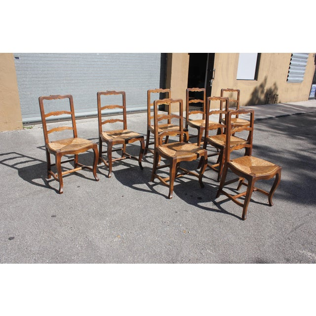 Set of 8 French country provincial ladder back chairs Circa 1910s. Solid walnut. Original rush seats. Cabriole legs...