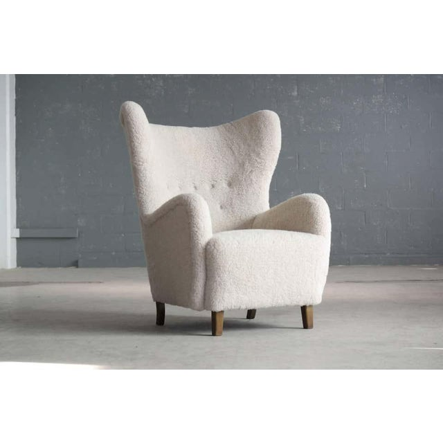 Beautiful Flemming Lassen attributed high back lounge chair in lamb's wool made in 1940s. This iconic ultra-elegant lounge...